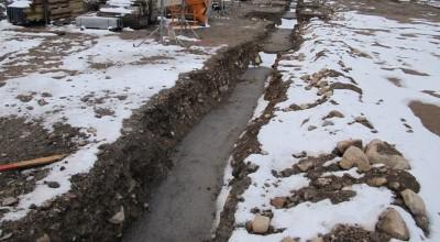 Die Rohplanie des Geländes haben wir noch im alten Jahr herstellen lassen, nun beginnen die Arbeiten mit dem Ausheben der Gräben für die Streifenfundamente und dem Einbringen einer Sauberkeitssicht.