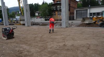 Während die einen Arbeiter den Boden für die Pflastersteine vorbereiten, kümmern sich die Anderen um den Graben für die Rohre.